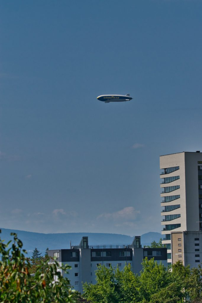 A Goodyear airship flying over Basel, residential buildings in the foreground.